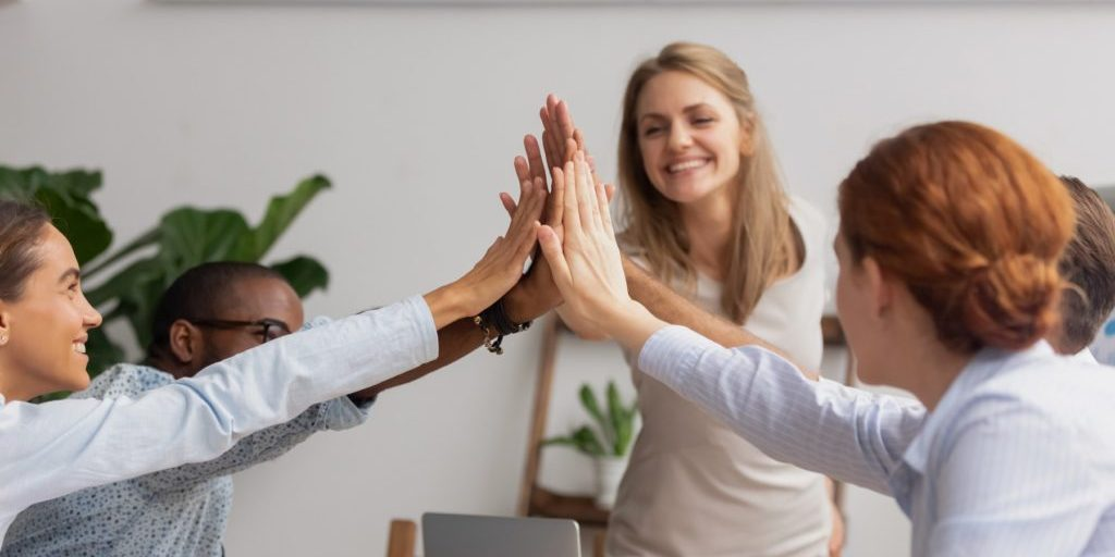 Reliable responsible happy diverse business team join hands give high five together, corporate alliance group celebrate goal achievement, engaged in teambuilding trust unity integrity loyalty concept